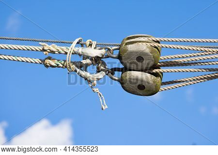 Wooden Pully At Ship With Ropework Against A Blue Summer Sky