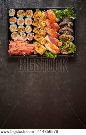 Sushi take-away plastic tray with diffent kinds of rolls and copy space. Take-away food concept.