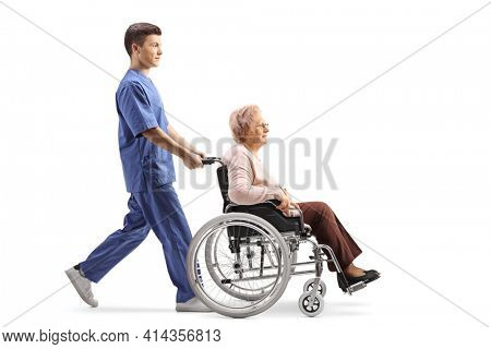 Full length profile shot of a medical worker pushing an elderly female patient in a wheelchair isolated on white background