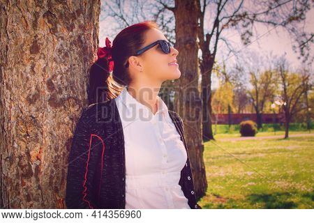 Beautiful Casual Smiling Young Girl With Glasses Leaning Against A Tree In The Park, Enjoying The Su