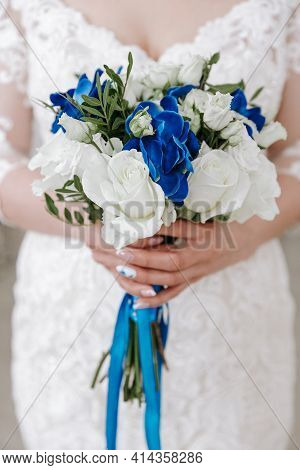 Wedding Bouquet Of White Roses And Blue Flowers In The Hand Of The Bride At The Ceremony, Blue Ribbo