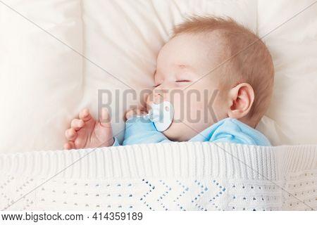 Seven Month Old Baby Sleeping On White Blanket And Pillow. Sleepy Child On Soft Bedding With Pacifie