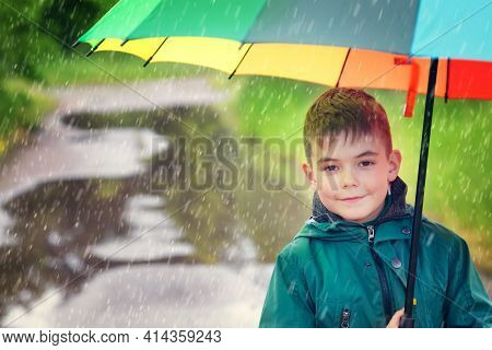 Child Walking In Puddle On Rainy Weather. Boy Holding Colourful Umbrella Under Rain In Summer