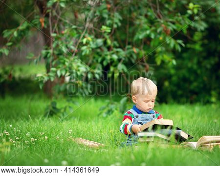 One Year Old Baby Reading A Book Sitting On The Grass In Garden
