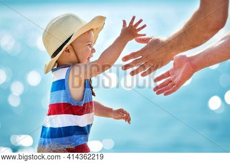 One Year Old Boy Playing With Father At The Beach In Straw Hat. Child On Family Vacations At Sea. Ma