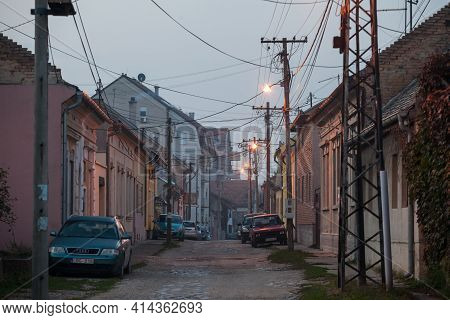 Pancevo, Serbia - October 25, 2020: Typical Unpaved Residential Street With Car Parks At Dusk In Pan