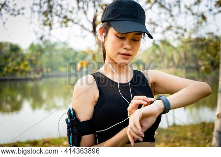 An Asian Women Runner Using Smart Watch To Monitor Her Performance. Athlete Setting Fitness App On S