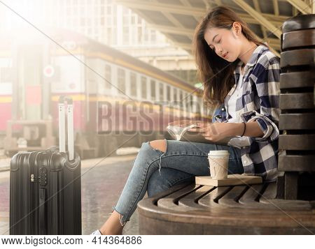 Travel Concept.beautiful Girl Reading Book Wating Train.woman In Plaid Shirt Waiting Train Sitting O