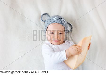 Baby Boy In Mouse Hat Lying On Blanket With Big Piece Of Cheese
