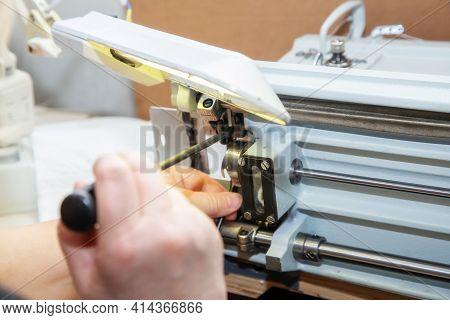Female Hands With A Screwdriver Repair The Shuttle Of The Sewing Machine. Repair Of An Industrial Se