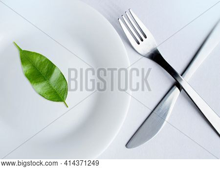 Vegan Lettering Made From Leaves On A Plate. The Letters Are Composed Of Leaves Folded Into The Word