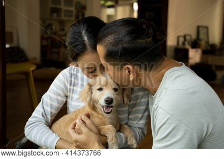 Diversity Young Couple Play With His Dog In The House. They Are Hugging Their Little Puppy. The Mode