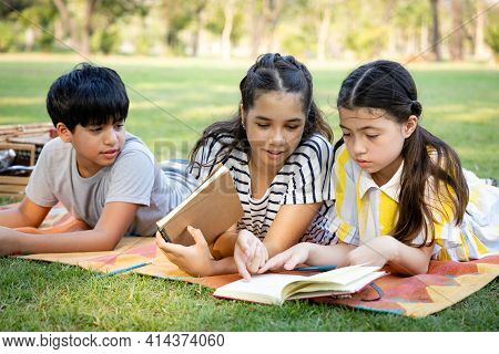 A Group Of Diversity Elementary School Children Enjoyed Lying Down And Reading In The Park. They Do
