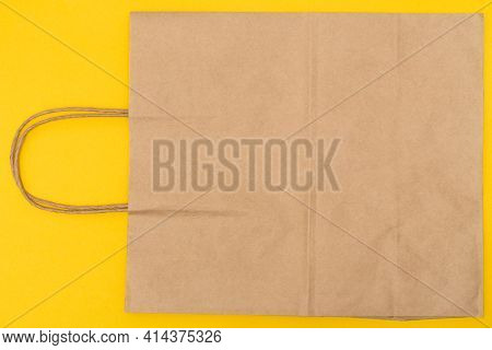 Paper Bag Over Yellow Background, Brown Shopping Bag. Craft Package With Handle. Packaging Template