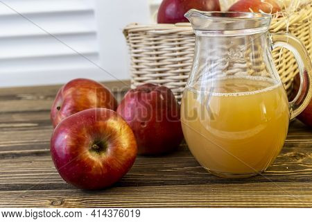 Red Apples In A Basket And Apple Juice In A Jug On A Wooden Table