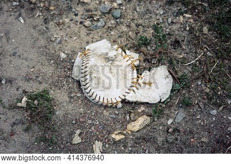 Used baseball flattened and splitting at the seams on the ground