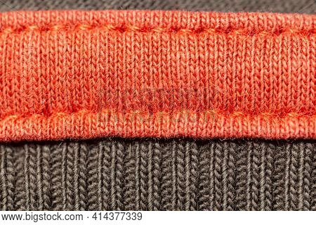 Bright Knitted Garment With Seams, Orange And Gray. Copy Space. Macro. Background.