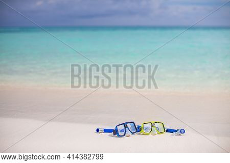 Diving Goggles And Snorkel Gear On Sandy Beach. Scuba Diving And Snorkeling. Two Snorkel On White Sa