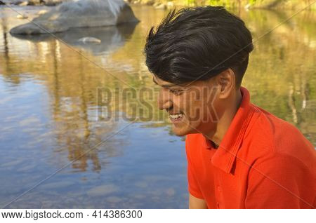 Close Up Of Side View Of An Indian Young Guy Smiling With Looking Sideways And Sitting In Beside Of