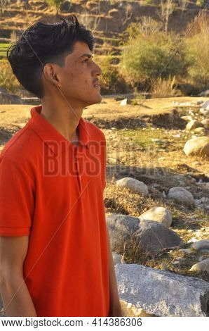 Portrait Of A South Asian Young Guy Standing In Outdoor And Looking Sideways, Young Man With Red Col