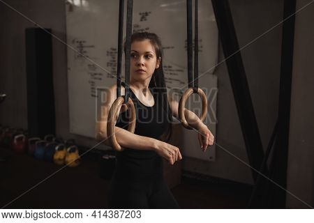 Female Gymnast Resting After Exercising On Gymnastic Rings