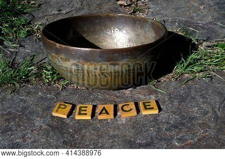 Tibetan Singing Bowl. In A Natural Environment. English Translation Of Mantra : Transform Your Impur