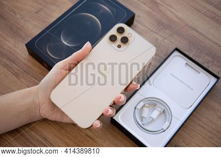 Alanya, Turkey - November 26, 2020: Woman Hand Holding Apple Iphone 12 Pro Max Gold And Sitting At T