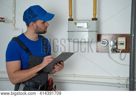 Man In Uniform Writes Down The Gas Meter Reading In A Notebook.