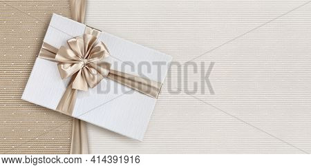 Gift Card, Gift Box With Beige Ribbon Bow Isolated On Elegant Pearly Fabrics Background, Top View An
