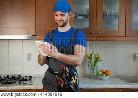Plumber Wearing A Tool Belt With Various Tools Using Tablet During Work In Kitchen