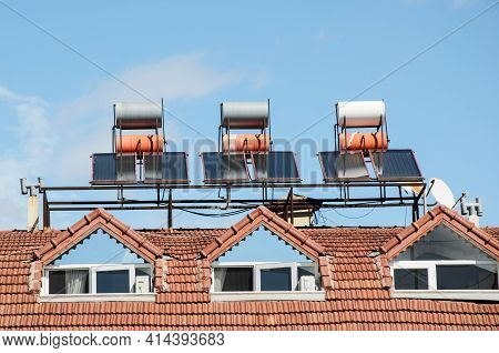 Solar Cells On The Tiled Roof Of A Residential Building. Solar Water Heating Panel And Barrels Of Wa
