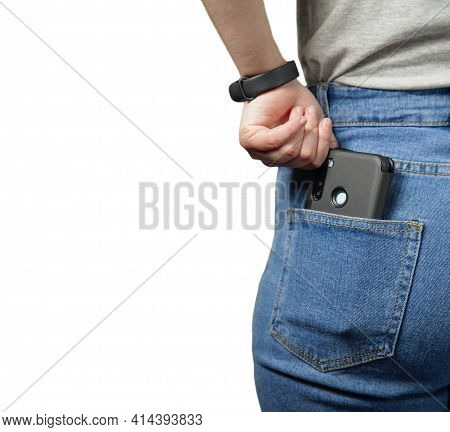 A Mobile Phone In The Pocket Of A Girl In Jeans. Isolated. At Close Range. The Girl's Hand Pulls The
