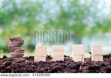 Money Growth With Environment. Stack Coin With Square Wooden On Soil And Green Blured Background. Pl