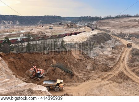 Excavator Load Sand In Heavy Mining Truck At Open-pit. Heavy Machinery Working In Mining Quarry. Pla