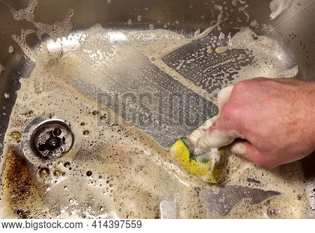 Sponge With Detergent And Foam While Washing The Sink In The Kitchen. Wash Dishes And Plumbing. Spon