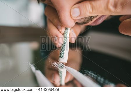 Close Up Of Junkie Man Sniffing Or Snorting Cocaine Lines On Mirror Through Rolled Dollar Banknote.
