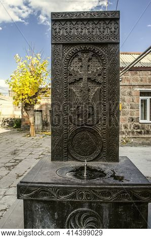 Khachkar Carved From Black Basalt With A Memorable Drinking Fountain On The Street Near A Residentia