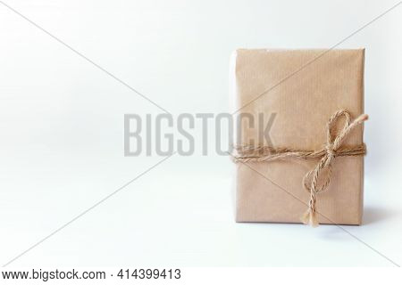 Rustic Gift Box Packed Into Brown Paper Tied By Twine With Blank On White Background With Space For