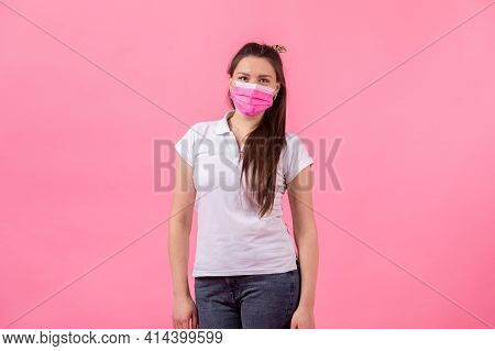 Beautiful Woman In Pink Medical Mask On A Pink Background. Woman Wearing Medical Mask. Protection Ag