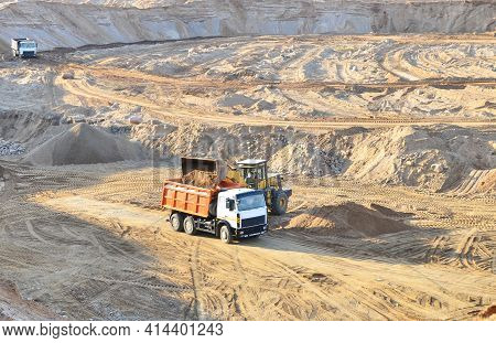 Wheel Front-end Loader Loading Sand Into Heavy Dump Truck At The Opencast Mining Quarry. Dump Truck