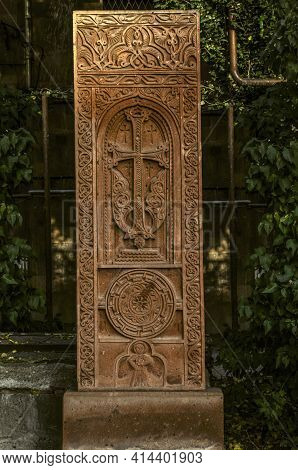 A Red Tuff Khachkar With A Floral Pattern Over An Arch With A Cross,a Figure Of A Saint And A Round