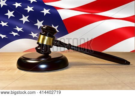Judge Hammer Against The Background Of The American Flag. Justice Concept In Courtroom. Mallet Of Ju