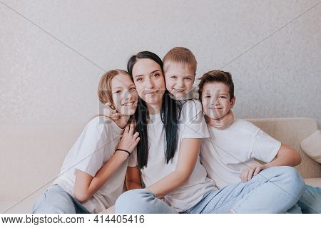 A Happy Mom Sits At Home On The Couch In The Arms Of Her Children. Understanding Supporting The Trus