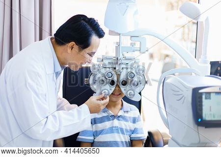 An Asian Male Doctor Examines A Child's Vision. Optometrists Man Are Examining Pediatric Patients' E