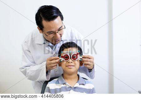 An Asian Ophthalmologist Examines The Child's Vision. An Optometrist Examines A Child's Eyesight Usi