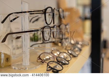 Close Up Glasses In Optics Store. Showcase With Spectacles In Modern Optical Shop.