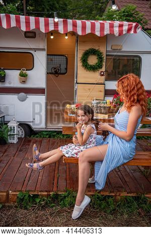 Young Red-haired Mother Braids Her Little Daughter's Braids On Wooden Bench By Trailer Truck. Matern