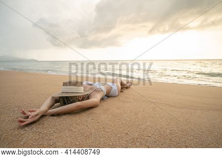 Woman In Bikini Lying Down On Sand Beach With Straw Hat Cover Her Face, Relaxing Sunbathing.