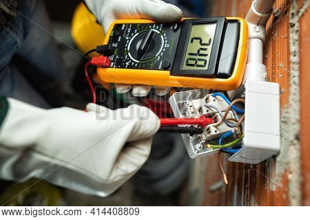View From Above. Electrician Worker At Work With The Tester Measures The Voltage In A Switch Of A Re
