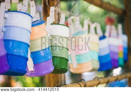 Still Life With Multicolored Food Carrier Or Tiffin Carrier Hanging On The Wood Stick. Selective Foc